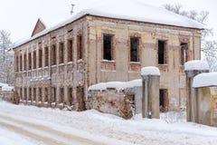 Een oude baksteen twee-storied geruïneerd huis in de straat van de kleine Russische stad in de winter stock foto's