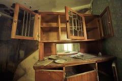 Een oude bediende in een verlaten huis in Pripyat: de deuren zijn wijd open, lege planken, allen in het stof, dichtbij de spiegel Stock Fotografie