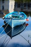 Een oude blauwe boot met kleurrijke oranje visserijvlotters dacht in kalm blauw water in een haven na royalty-vrije stock foto's