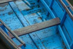 Een oude blauwe houten boot op het water stock foto's