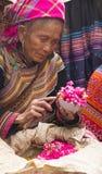 Een oude, blinde, Bloem Hmong verkoopt kleurrijke rijst in Bac Ha Stock Afbeelding