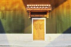 Een oude Chinese deur in een verlichtende muur Stock Foto's
