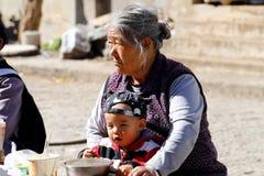 Een oude Chinese vrouw met een klein kind op de weg in het dorp van Shigu, Yunnan, China stock fotografie