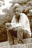 Een oude dakloze mens met tulband en baard het stellen voor een foto stock foto