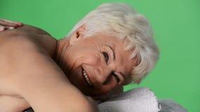 Een oude dame die bij kuuroordsalon liggen. stock video