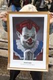 Een oude dame die de karikatuur van Milos Zeman houden die als kwade clown bij de demonstratie op het vierkant van Praag wordt ge Stock Foto