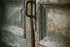 Een oude deur met een roestig handvat en een sleutelgat stock foto's