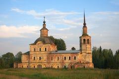 Een oude die dilapidated kerk met bomen in het platteland tegen een blauwe die hemel met wolken wordt overwoekerd door groen word stock afbeeldingen