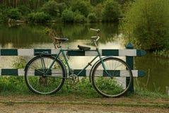 Een oude fiets bevindt zich dichtbij een houten omheining op de waterkant stock foto