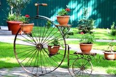 Een oude fiets met bloemmanden voor het verfraaien van parken en tuinen stock foto's