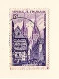 Een oude Franse postzegel met een beeld van een kerk en oude huizen stock foto