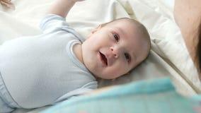 Een oude gelukkige pasgeboren baby van twee maand ligt op het bed en ervaart emoties aan zijn moeder Een baby lacht, spreekt, gol stock footage