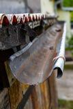 Een oude goot in een losgemaakt huis Regenwaterdrainage van het dak stock afbeeldingen