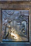 Een oude hulp onder het standbeeld van St John van Nepomuk op Charles Bridge in Praag, Tsjechische Republiek stock afbeeldingen