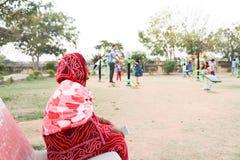 Een oude Indische damezitting op de bank en de lettende op kinderen die in een open gymnastiek in een park spelen stock foto's