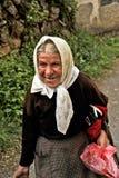Een oude Macedonische dame die omhoog de straat met een emmer in haar hand lopen Stock Foto's