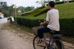 Een oude mens berijdt een oude fiets door een park in Laos, Azië Achter mening royalty-vrije stock afbeelding