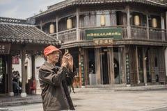 Een oude mens die een oranje hoed en glazen dragen en foto's met zijn mobiele telefoon in het toneelgebied nemen Royalty-vrije Stock Foto's