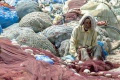 Een oude mens die reparaties uitvoeren aan een visnet bij de haven van Essaouira in Marokko Royalty-vrije Stock Afbeeldingen