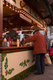 Een oude mens die wat voedsel op een Kerstmismarkt kopen in Goettingen, Duitsland stock foto's