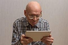 Een oude mens houdt een tablet royalty-vrije stock afbeeldingen
