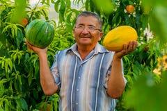 Een oude mens met een meloen en een watermeloen Stock Foto
