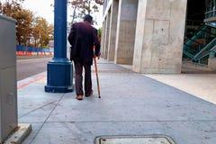 Een oude mens met een riet die onderaan de stoep lopen stock afbeelding