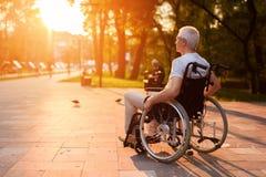 Een oude mens zit in een rolstoel en let op de zonsondergang in het park royalty-vrije stock foto's