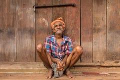 Een oude mensenzitting dichtbij de houten muur in Gokarna, India Royalty-vrije Stock Fotografie