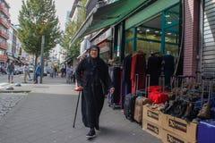 Een oude Moslimdame in zwarte kleren en een headscarf en glazen loopt onderaan de straat stock foto's
