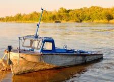 Een oude motorboot bij de bank van de rivier stock foto