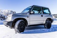 Een oude offroad auto op de sneeuw Stock Afbeeldingen