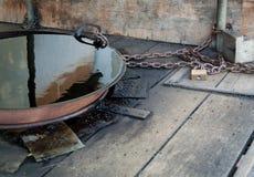 Een oude olie - gevulde die pan aan post wordt geketend stock fotografie