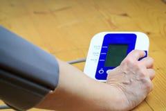Een oude oudste/een vrouw bereidt het meten van bloeddruk door electr voor Royalty-vrije Stock Foto