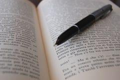 Een oude pen die op een boek ligt! Stock Foto