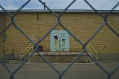 Een oude roest en een wintertaling kleurden deur op de oude fabrieksmuur door de omheining stock fotografie