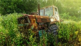 Een oude roestige verlaten die tractor in een boerenerf binnen onder overwoekerd gras en onkruid wordt geparkeerd stock foto's