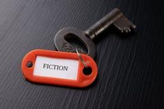 Een oude sleutel met een inschrijving op een zwarte lijst Toebehoren en symbool die naar het woord in de beschrijving van de sleu stock fotografie