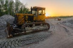 Een oude tractor met een grote emmer haalt zand in een steengroeve Royalty-vrije Stock Foto's