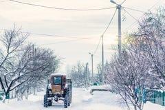 Een oude tractor op de achtergrond van een de winterstraat Stock Foto