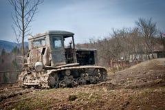 Een oude tractor wordt verlaten in vuil Stock Foto