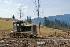 Een oude tractor wordt verlaten in vuil Royalty-vrije Stock Foto's