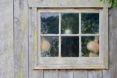 Een oude tuinloods of weinig die huis, en doorstaan, met sommige tuinhulpmiddelen verlaten is verouderd naast het royalty-vrije stock afbeeldingen