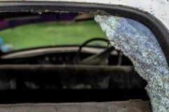 Een oude uitstekende auto in een slechte voorwaarde met gebroken achterruitruit stock fotografie