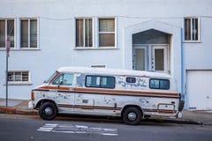 Een oude uitstekende bestelwagen parkeerde buitenkant op de weg stock foto