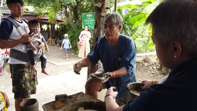 Een oude vakman bewerkt Thais traditioneel aardewerk stock footage