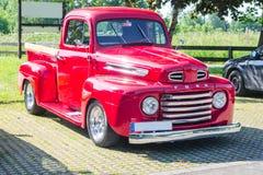 Een oude vernieuwde rode uitstekende bestelwagen van Ford in een parkeerterrein Stock Fotografie