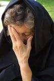 Een oude vrouw behandelt haar gezicht Royalty-vrije Stock Fotografie