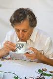 Een oude vrouw blaast bij hete thee terwijl het hebben van haar ontbijt royalty-vrije stock fotografie