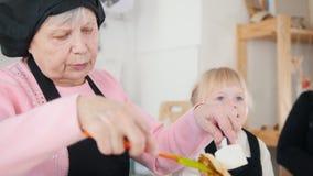 Een oude vrouw die pannekoeken in de heldere keuken maken en met een klein meisje spreken stock footage